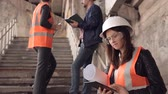 determinado : A woman Builder or architect works on a tablet and then looks at the camera. In the background, talking to the builders Stock Footage