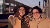 bíblico : mom and adult daughter in glasses at the railway station look at the camera and smile at the video portrait Stock Footage
