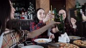 pizza restaurant : several girls eat pizza and drink beer from bottles in the restaurant. Talk laugh and celebrate Stock Footage