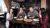 pizza restaurant : a group of young people drink beer and eat pizza in a restaurant