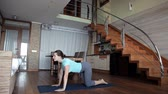 posição : Young sporty woman working out at home, doing fitness exercises on living room floor using online personal training program, doing yoga pilates indoors