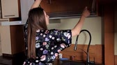 опрятный : Young girl washing dishes in the kitchen
