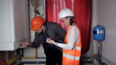 zawór : The inspector and the worker check the heating system. Beautiful woman engineer