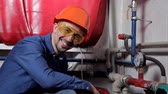 zawór : An engineer in glasses works in the boiler room, checks the maintenance of the heating system equipment Wideo