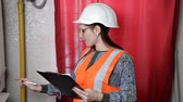 zawór : Female engineer checks the data of the heating system equipment in the boiler room