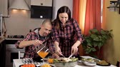 doldurulmuş : A young couple made dinner, salads, vegetables, a young girl cuts a fried chicken, a young bald guy pours juice into a glass Stok Video