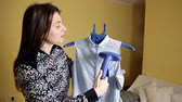 cottura a vapore : Young girl stroking her blouse with vertical steam iron at home