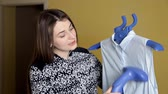 kledingkast : Young girl using steam system for Ironing clothes. Steamers blue blouse at home