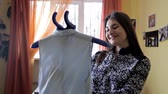 wasserij : A woman uses steam to iron her blouse. The process of steaming the blouse using a steam cleaner. Close up Stockvideo
