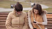 assise : Mother and daughter sitting in the park to communicate, use mobile phone. Nature, relationships Vidéos Libres De Droits