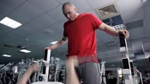 halter : Man raises free weight under control of instructor in sports club. Handsome guy lies on bench and does exercise with iron object Stok Video