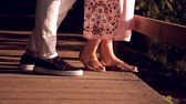 pantolon : lovers on a wooden bridge at sunset. close-up legs Stok Video