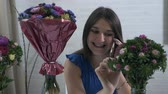 krizantem : A young girl at home puts bouquets of flowers in a cart with water and speaks on the phone