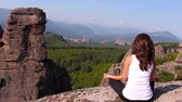 vale : Woman doing yoga exercises on Belogradchik rocks, admiring the Belogradchik valley Stock Footage