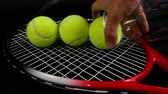 árbitro : Hand putting set of three new tennis balls over tennis racket on black background