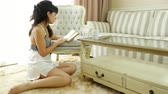 camisola : Woman in a nightdress is reading a book at home a cup of coffee on the table Vídeos