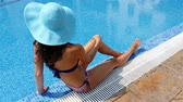 banho de sol : Young woman in swimming suit and blue hat sitting on the edge of a swimming pool and taking sunbath