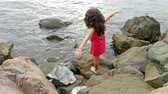 banho de sol : Little girl in red summer dress sitting on the rocks on the sea shore