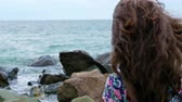 banho de sol : Little girl in a dress standing on the rocks on the sea shore and looking to the stormy sea Vídeos