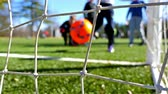 outside : Children playing soccer game, camera behind the goal net