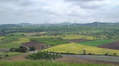 jeju island : Picturesque Landscape of farm field with wind generator, view from Yongnuni Oreum (Yonganak), a parasitic volcano in Jongdal-ri, Jeju, Korea.