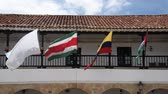 Colombian and other flags blowing in the wind on a balcony in Villa de Leyva, Colombia Stock Footage