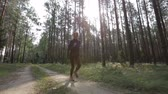 stabilizer : Happy young woman is jogging in a forest among trees. Tracking shot with stabilized camera Stock Footage