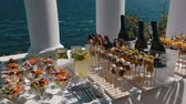 obiad : Reception table with wineglasses fillled with fresh salad. Focus panorama of table served outdoors near the sea