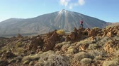 rocky mountains : Young Woman arms outstretched observes a huge crater of Teide volcano, Tenerife, Canary islands, Spain. Aerial drone view of a volcanic desert. Stock Footage