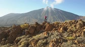 rochoso : Young Woman arms outstretched observes a huge crater of Teide volcano, Tenerife, Canary islands, Spain. Aerial drone view of a volcanic desert. Stock Footage