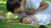 Mother kisses her Baby sleeping on a green grass Outdoors. Happy young Mother and Child in Green Summer Park. Beautiful family in spring park enjoying nature.
