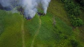 basureros : Flight through a smoke from burning green field, wild fire in nature landscape, aerial footage from drone