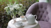 waterglas : Hot tea in white cups served outdoors on a white table decorated with a bouquet of flowers.