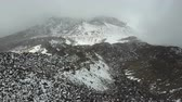 rochoso : Aerial view of the crater of a volcano pico Viejo on Tenerife, covered with snow and clouds.