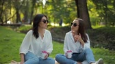 elfog : Two stylish happy smiling girls in white shirts are sitting in the park on a soft background of green foliage. Girlfriends have fun, discuss important issues, drink coffee in paper cups. Stock mozgókép