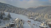 chalet : Flight over a a ski resort in Carpathian mountains and a village. Aerial view of snow-covered houses in mountains. Rural landscape in winter. Carpathian village in the snow from a height.