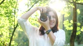 elfog : Pretty smiling girl photographer in white shirt is making photos in a park on a soft background of green foliage. A woman photographs model looking at the camera through the rays of the sun at sunset. Stock mozgókép