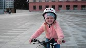 meninos : Little smiling happy girl in a pink jacket and a boy ride green bicycle and run bike in sunset light in a city. Little Bikers with helmets follow a moving camera.