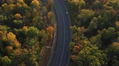 сентябрь : Epic aerial flight over autumn forest and road. Cars drive along the road along the park, the atmosphere. Aesthetics of autumn nature. Beautiful sunset on the yellow and red leaves of the trees.