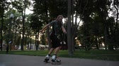 meninos : Young long-haired bearded man roller skater is dancing in a nice evening in a city park. Freestyle Roller skating at sunset.