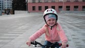 meninos : Little smiling happy girl in a pink jacket is riding on green bicycle in sunset light in a city. Little Bikers with helmets follow a moving camera. Stock Footage