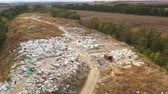 teherautó : Aerial view of Packed Waste on a landfill. Employees and Scavengers are processing waste on a rubbish dump. Large garbage pile at sorting site.