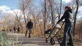 meninos : Roller family walks in autumn with baby in a cozy, city park. Dad dances and entertains the baby. Bright, sunny day, Slow motion. Sports education and healthy passion.