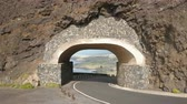 sarma : Flight out of a tunel. Drone flies along a passway through a rock. Aerial view of Punta del Fraile, Tenerife, Canary Islands, Spain Stok Video