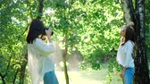 looking at camera : Pretty girl professional photographer wearing white shirt is making photos of a happy smiling girl in a park next to a birch tree on a soft background of green foliage and spraying water. Stock Footage
