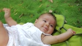 érdekes : Infant baby child Little girl lies on a rug on grass in a park. Dreamy newborn baby infant lying on a grass outdoors.
