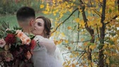 evlenmek : Close-up portrait of Groom and bride hugging near a lake in autumn forest among Colored fall trees. Young attractive Happy loving newlyweds in a park in Slow motion.