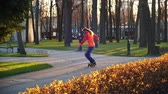 szyszka : Sporty and useful rollerblading. A man professionally trains on roller skates, rides between training cones and performs complex turns in the city park in the last days of autumn. Slow motion.