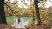evlenmek : Wedding in the woods in nature. Groom and bride hugging near a lake in autumn forest among Colored fall trees. Young attractive Happy loving newlyweds in a park in Slow motion.