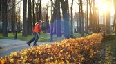 walze : Nimble man on roller skates makes sharp turns and masterfully rides between training cones in a cool city park under the warm sun. Active and healthy leisure and lifestyle. Side view in slow motion.